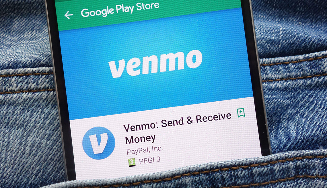 Venmo app on Google Play Store website displayed on smartphone hidden in jeans pocket