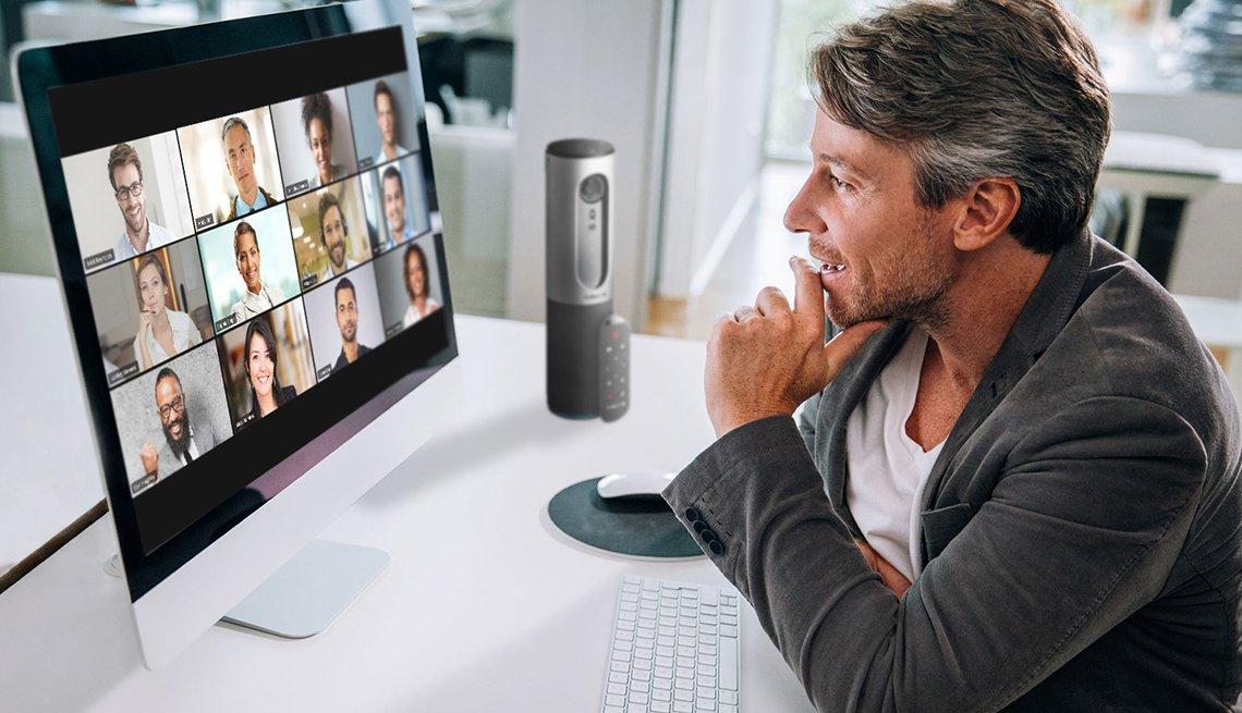 Hombre en su escritorio interactuando en una reunión de Zoom