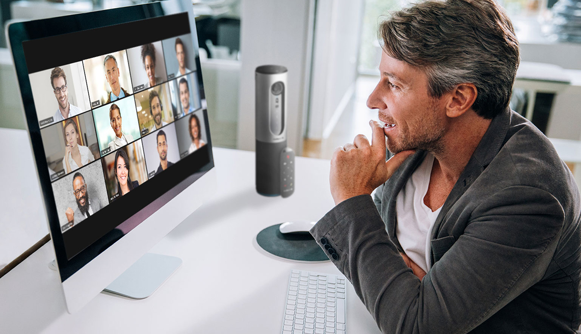 man at his desk interacting with a zoom meeting showing on a large monitor in front of him