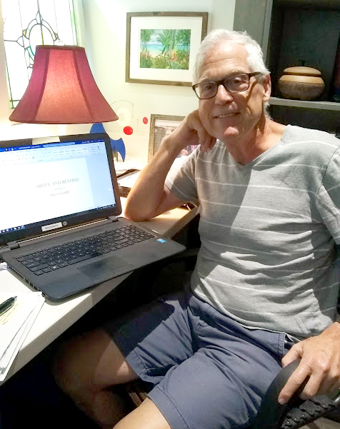 a man sitting at a desk in his home office turns from his laptop to smile for the camera and show the title of the book he is writing on the laptop monitor