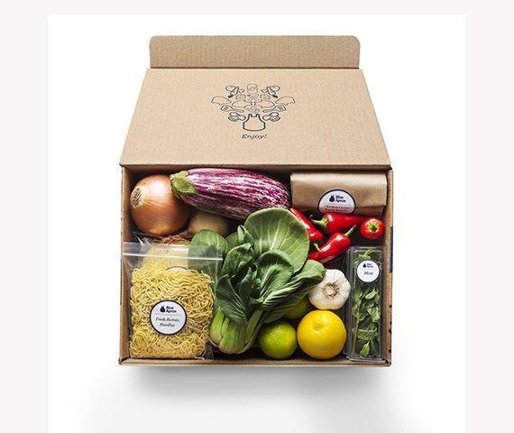 Caja abierta llena de verduras, arroz y comida variada