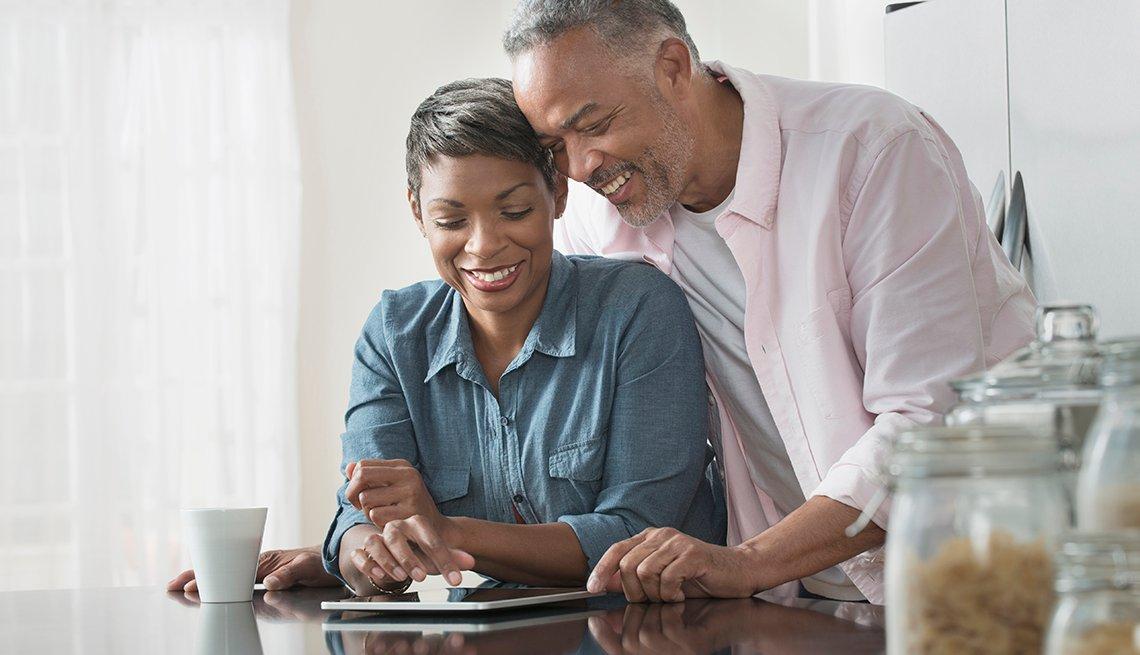 Pareja usando una tableta digital en una mesa de cocina