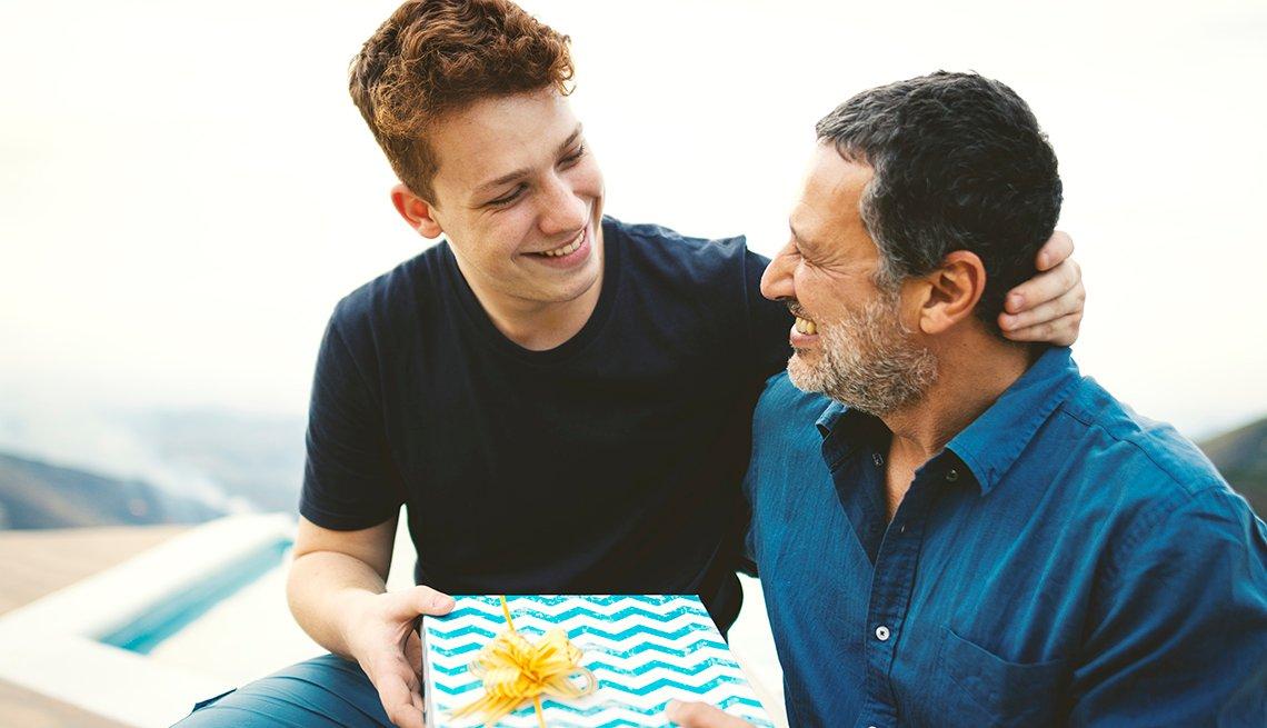 Adolescente entrega un regalo a su padre