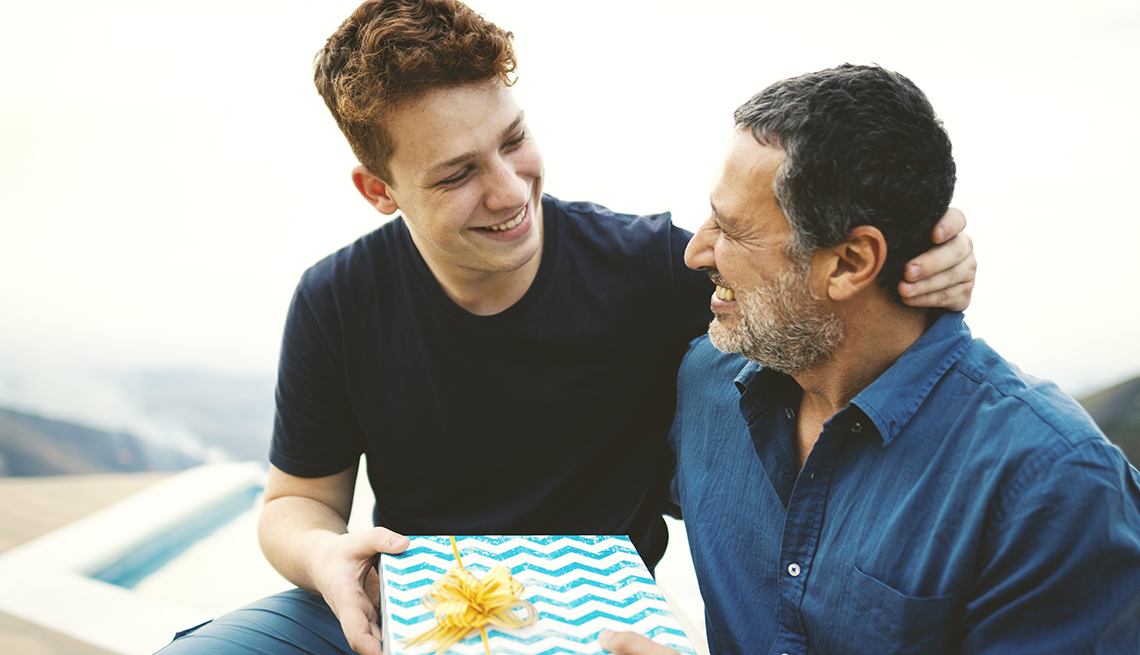 Teenager giving a gift for his father outdoors in the nature.
