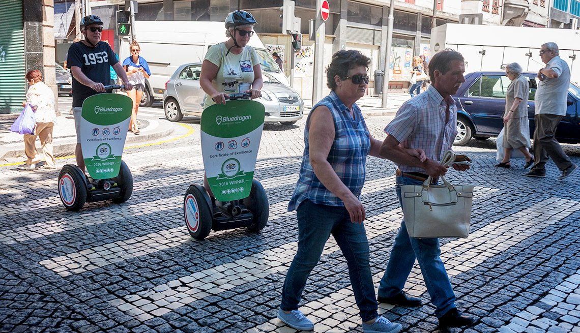 Two pedestrians cross the cobbled Rua Sa da Bandeira, followed closely by a pair of Segway riding tourists.