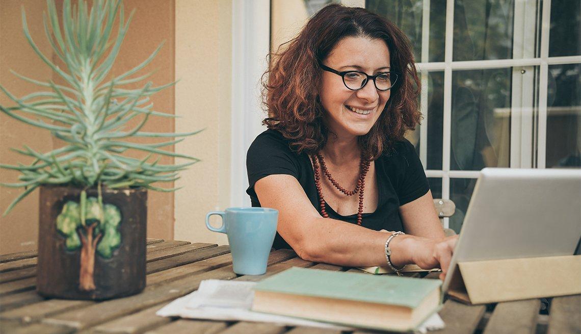 Mujer en casa con libros, periódicos y una tableta electrónica