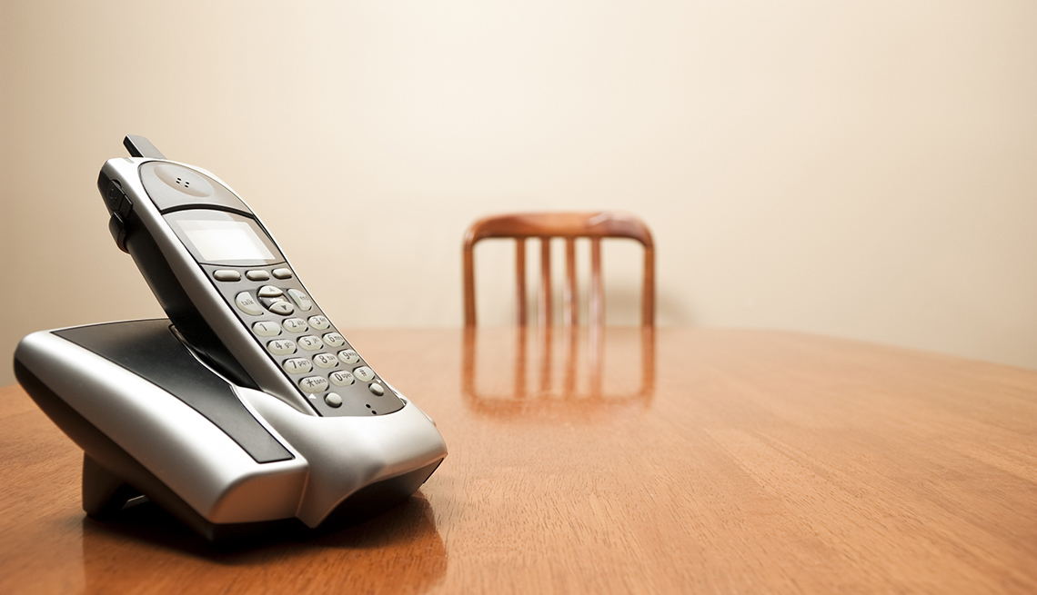A modern cordless phone sits on an empty table. Focus on phone in foreground.