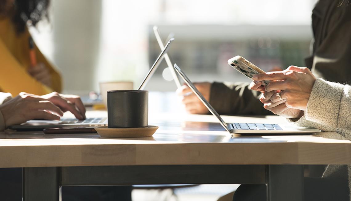 Dos personas con sus computadoras y sus teléfonos sobre una mesa.