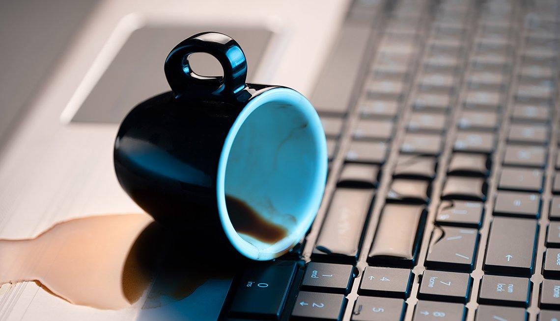 Taza de café derramada sobre el teclado de una computadora