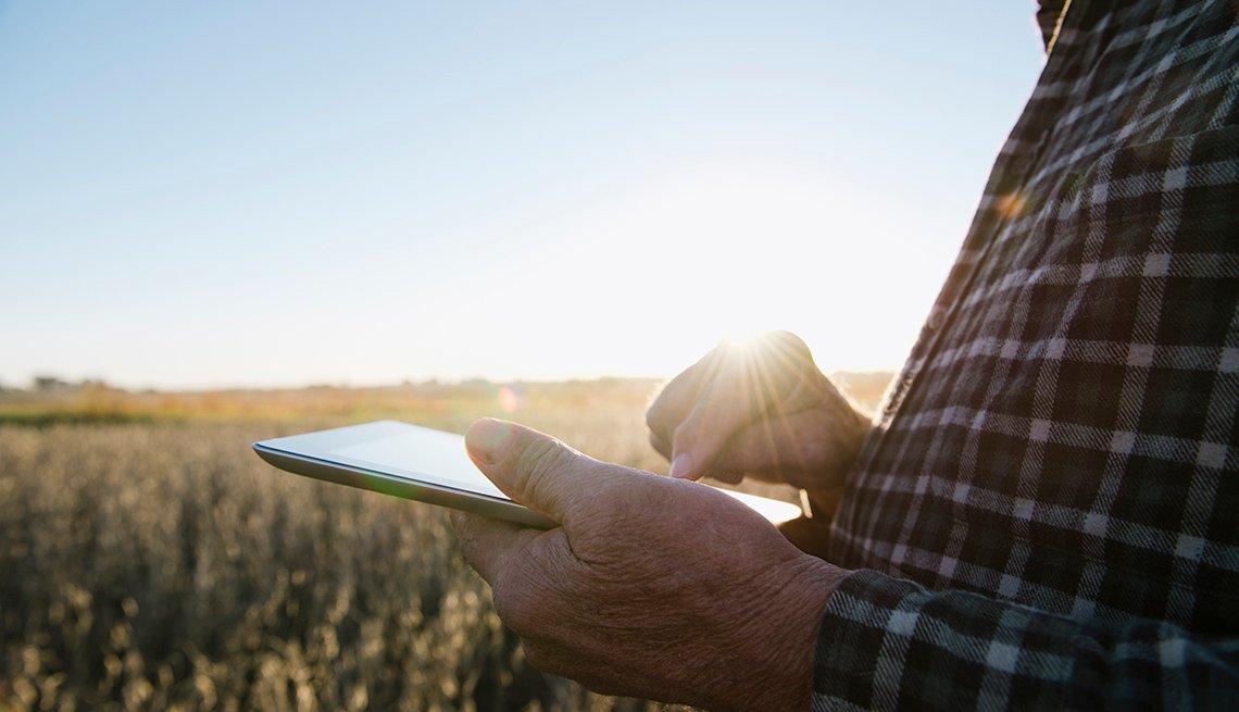 Un hombre sostiene en sus manos una tableta electrónica