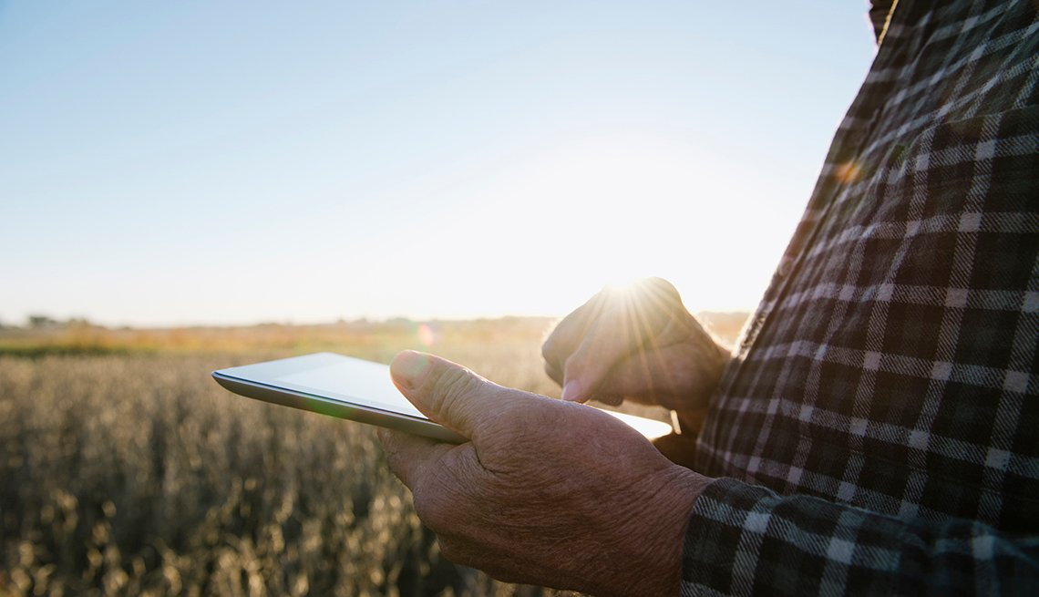 Man holding a tablet in a field