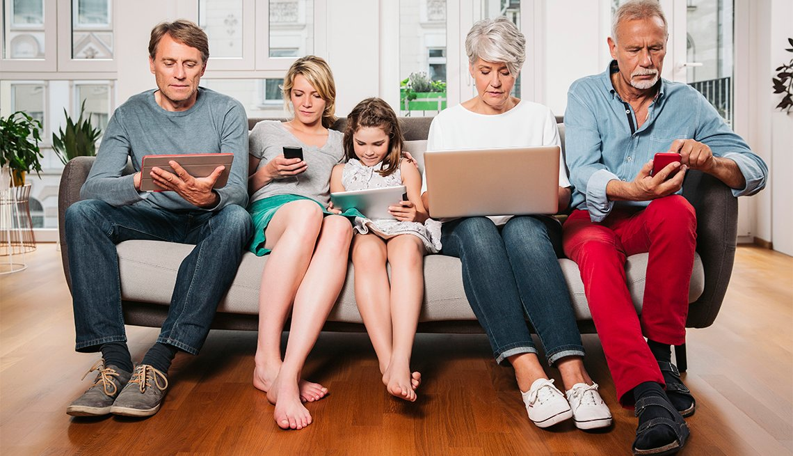 Family of three generations sitting on one couch, busy with one device each, Cologne, NRW, Germany
