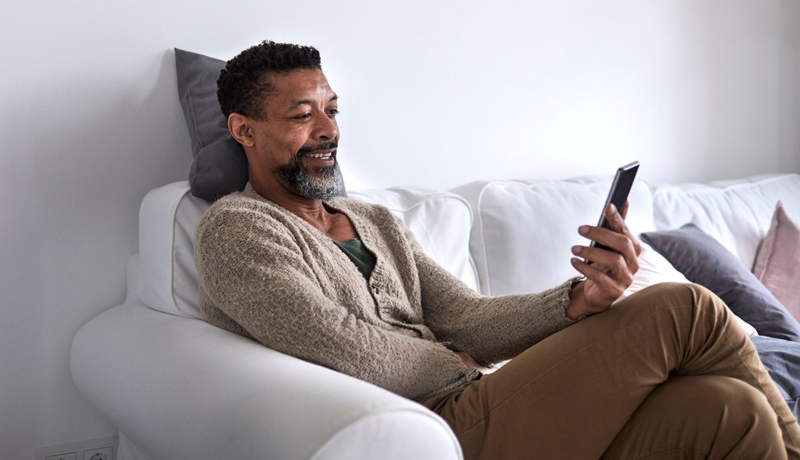 Man smiling, laughing at smartphone