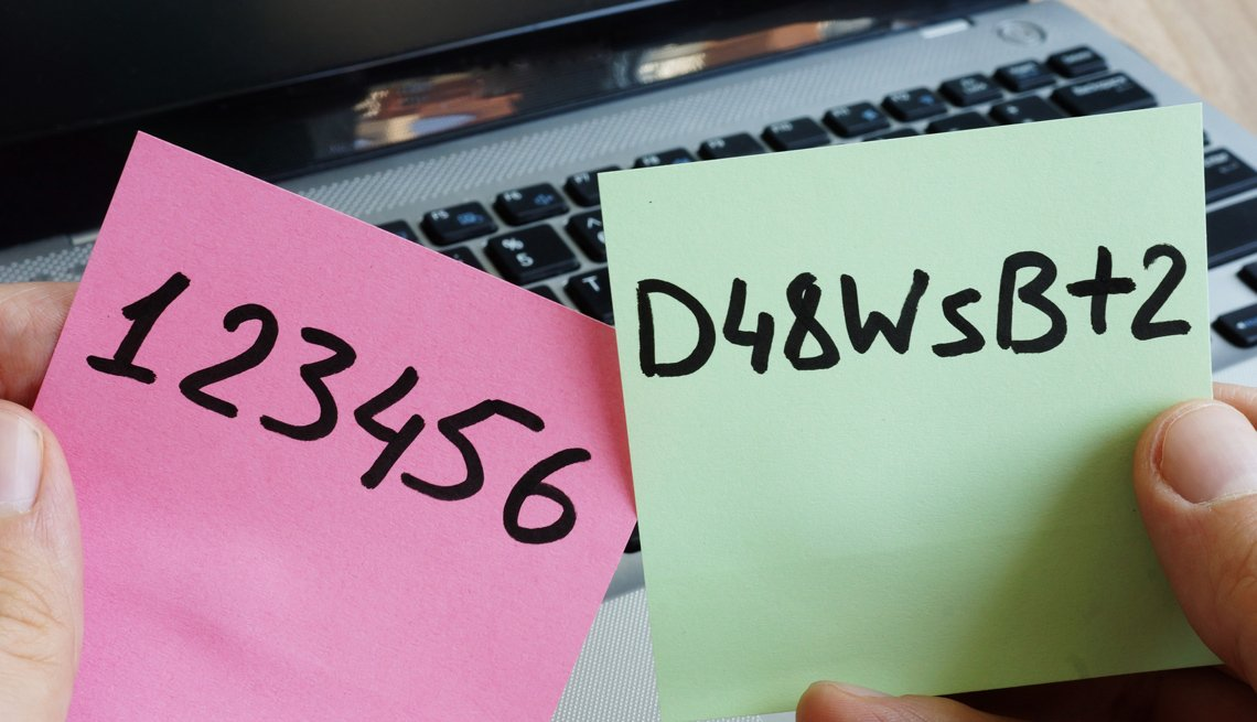 Persona frente a su computador observa dos contraseñas anotadas en hojas de papel