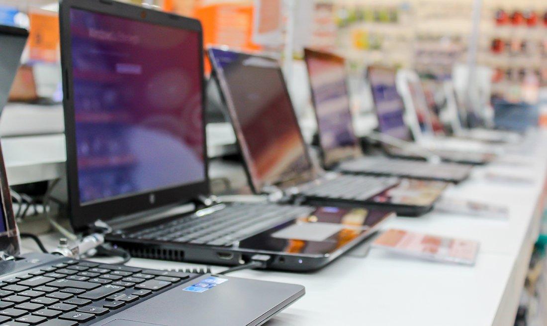 Línea de computadores portátiles en una tienda de tecnología