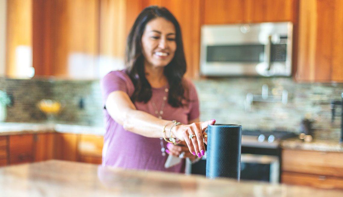 Mujer en su cocina tocando un dispositivo de altavoz inteligente