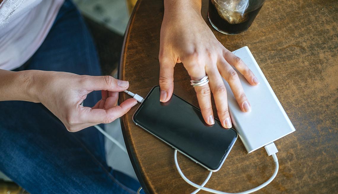 Mujer conectado su teléfono a una batería portatil