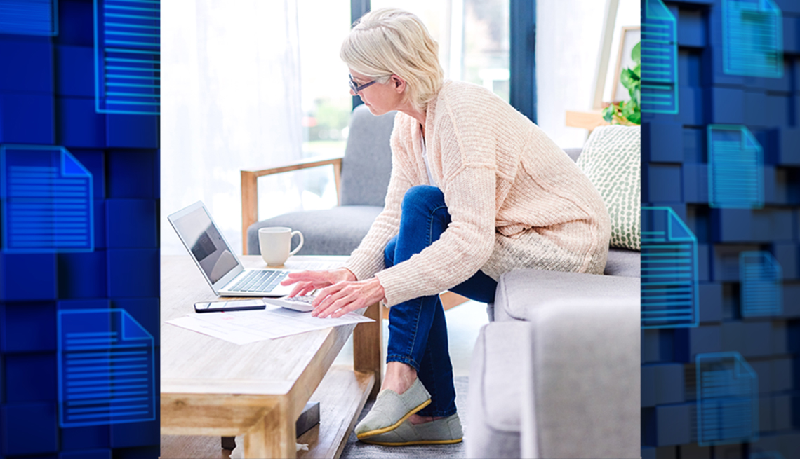 a woman doing digital asset planning on her laptop at home and the background shows digital files