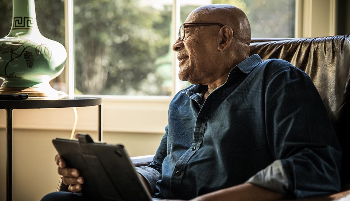 Un hombre mayor usa una tableta electrónica en su casa