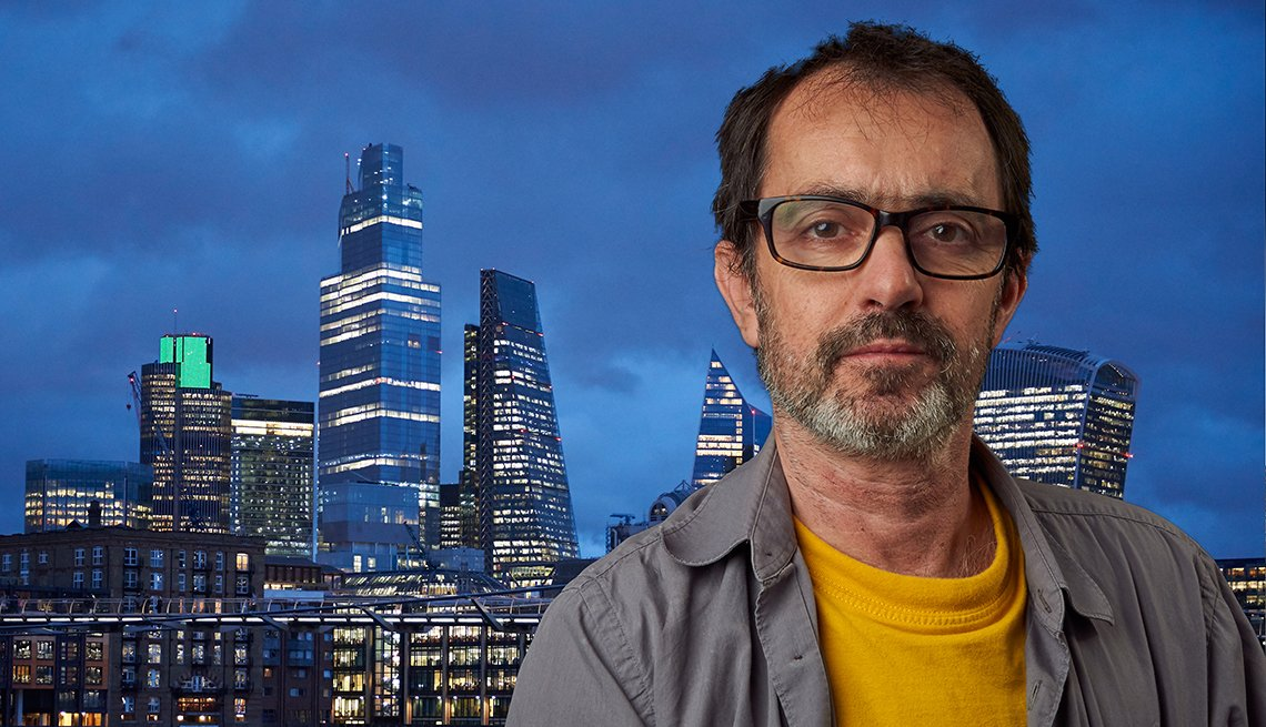 Man wearing glases sits in front of obviously fake tv like background.Wearing a grey shirt and yellow T-shirt. skyscrapers and blue sky