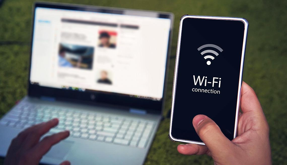 Una persona trata de conectar su computadora a la red wifi de su teléfono