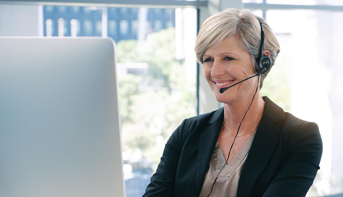 Mujer usa audífonos al trabajar en una computadora