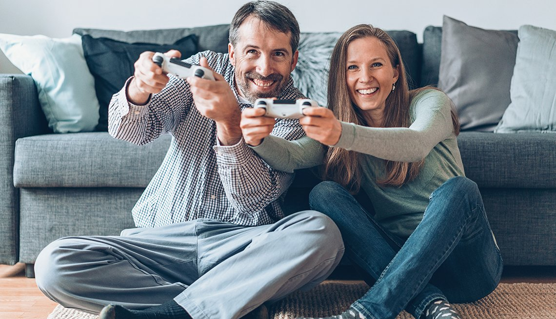 Happy couple playing video games together at home