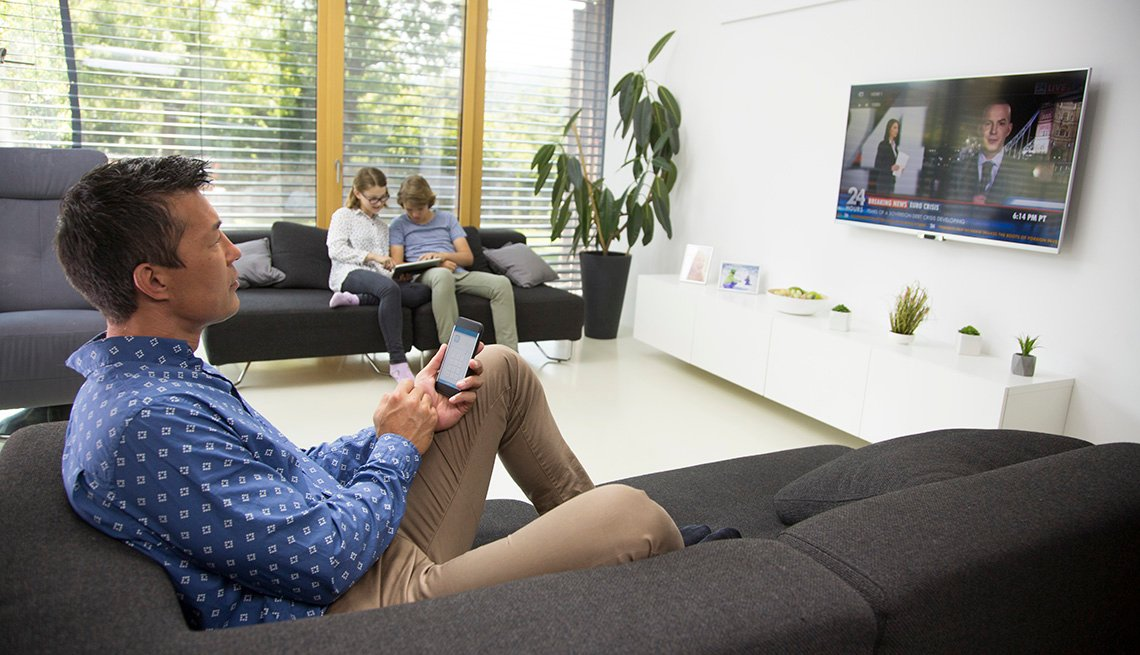 Mature man sitting on sofa and controlling smartphone while watching tv, kids using digital tablet in background.