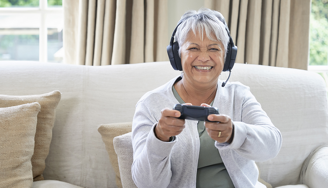 A woman playing video games in her living room with headset on