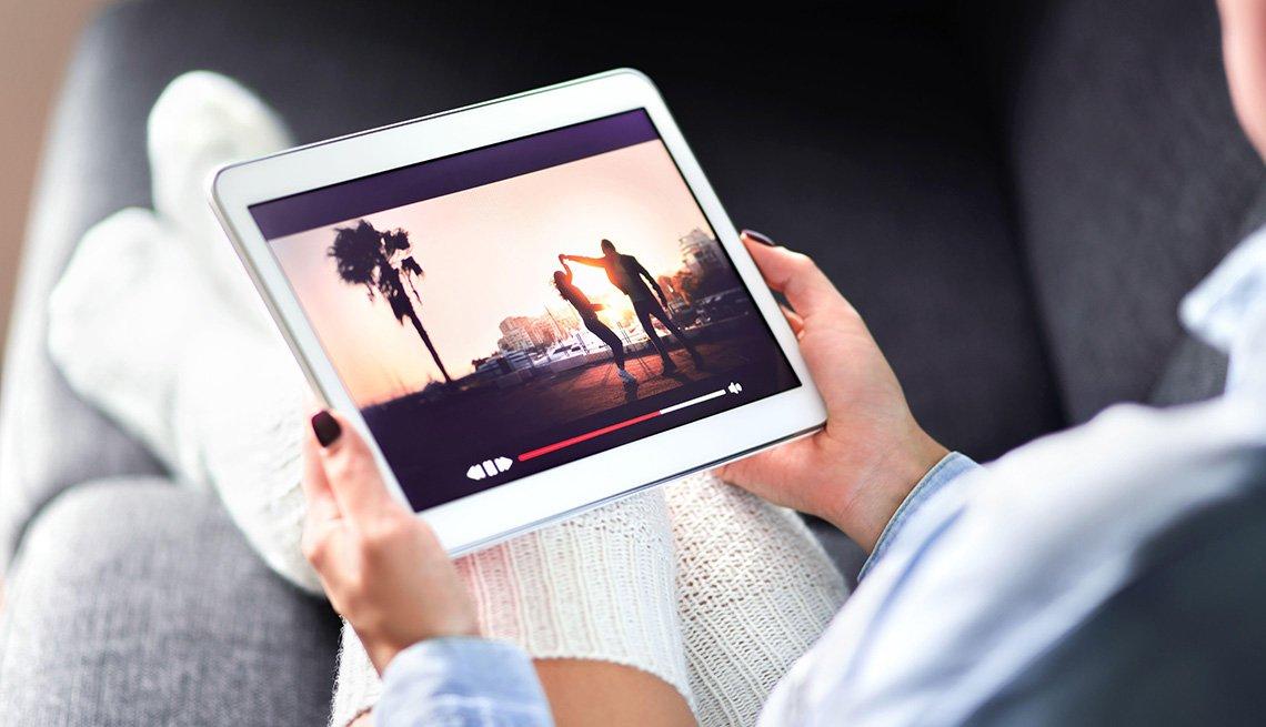 Persona ve una película en una tableta electrónica