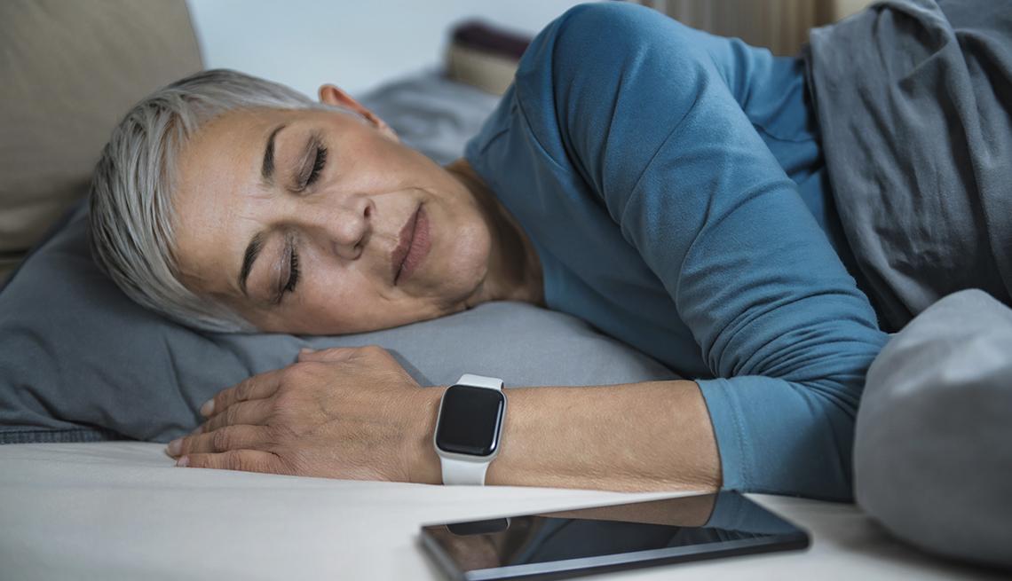 Una mujer duerme junto a su teléfono inteligente