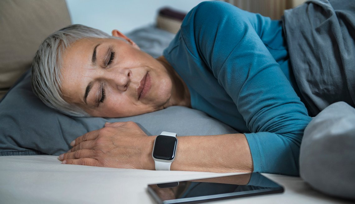 A woman is sleeping next to her smartphone