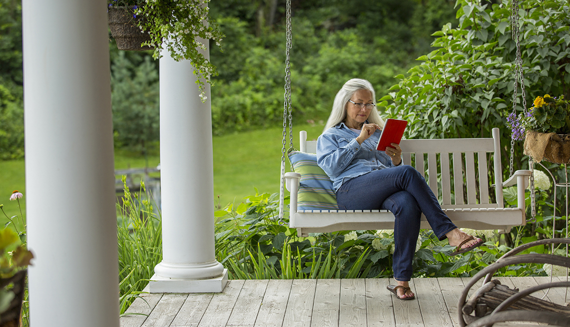 Woman using digital tablet on porch swing