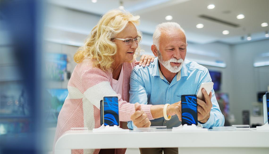 Un hombre y una mujer observan un teléfono inteligente