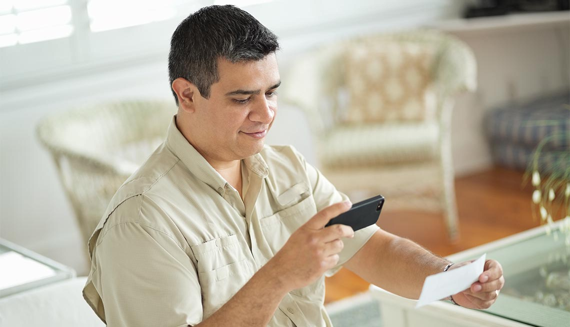 man using smart phone to scan and deposit check at home