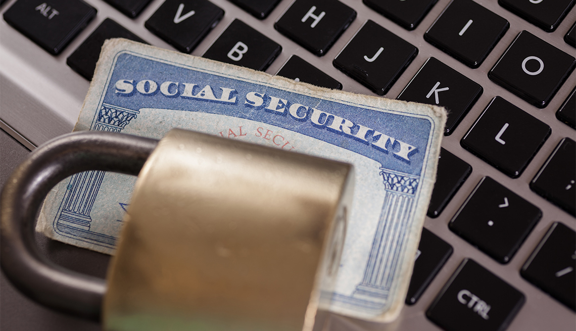 a social security card with a lock on a computer to illustrate cyber crimes