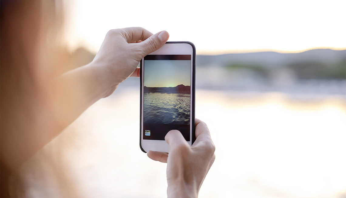 close up of a woman holding a smartphone taking a picture of a sunset