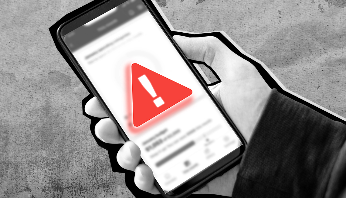 Una mano sostiene un teléfono celular con un símbolo de advertencia