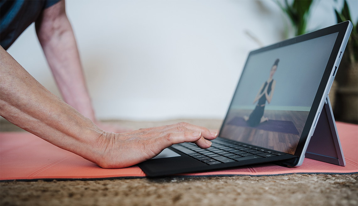 person using a tablet to watch a yoga tutorial video