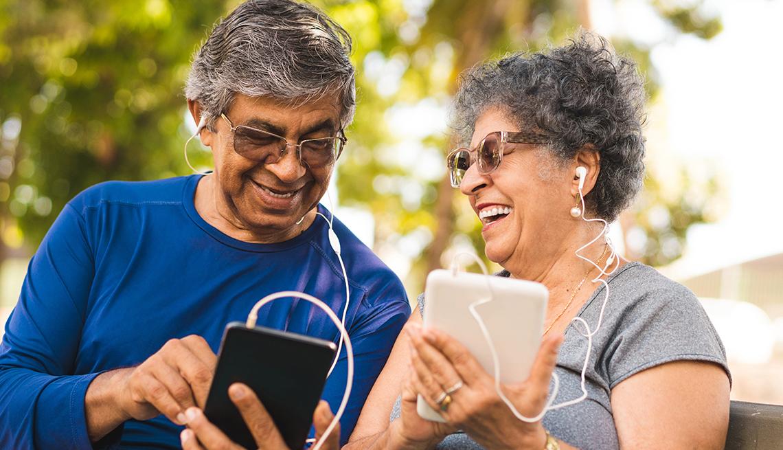 Un hombre y una mujer sonríen mientras están sentados en un parque
