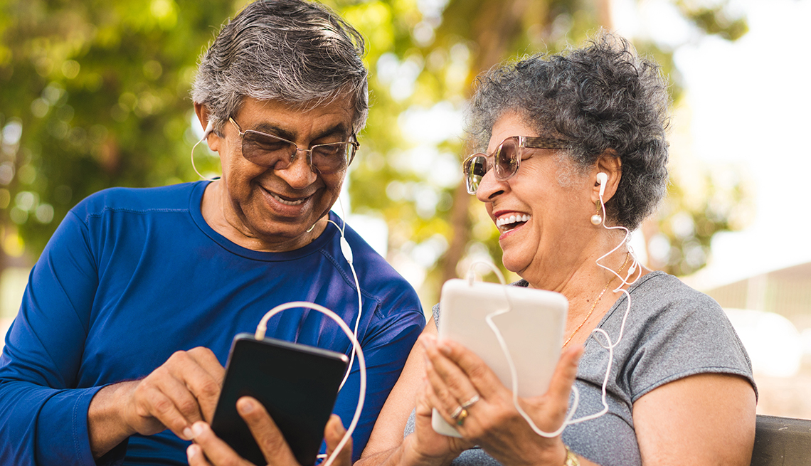 smiling couple seated in a park plugged into mobile devices