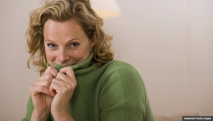 How to feel better about your body in bed- a shy woman in a turtleneck sweater
