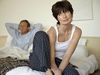 Pareja sentada en su cama - Acercarse a su pareja acerca de los problemas íntimos requiere confianza, ánimo y delicadeza.