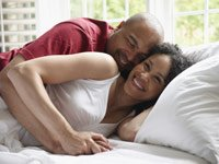 couple smiling in bed. love, marriage, and sex.