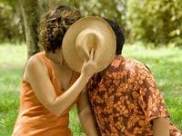 Pareja sentada en un césped con un sombrero delante de su cara mientras se besa - San Valentín