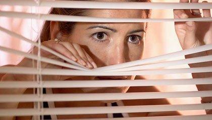 Mujer mirando a través de las persianas - Los celos en una relación