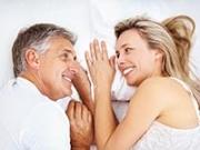 Pareja sonriendo en la cama. Lubricantes personales son buenas para los hombres también.