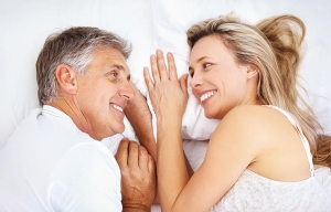 Couple smiling in bed. Personal lubricants are good for men, too.