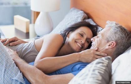 Pareja sonriendo en la cama, gran sexo a pesar de la artritis