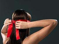 Mujer se ata una cinta sobre los ojos - La alegría de los ojos vendados en los juegos sexuales